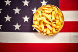 top view of delicious french fries on a wooden plate on the background of the USA flag - 233043355