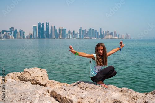 Leinwanddruck Bild Little Child Girl Sitting on Corniche Broadway and Looking on the Doha Skyline View. Qatar, Middle East.