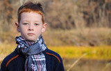 child in a checkered scarf on the background of the autumn river, blurred background, close-up.