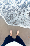 Blue waves in the sand with male feet
