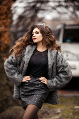 Portrait of stylish young girl in grey coat after beauty salon keeping bag, looking at camera and posing outside. Pretty woman with makeup and volumetric curls wearing cat ears. Concept of fashion. © Вячеслав Косько