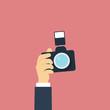 Hand holding photo camera. Flat design style. Vector illustratio