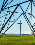 Wind Turbine seen through frame of an electricity pylon with blue sky - 233052534