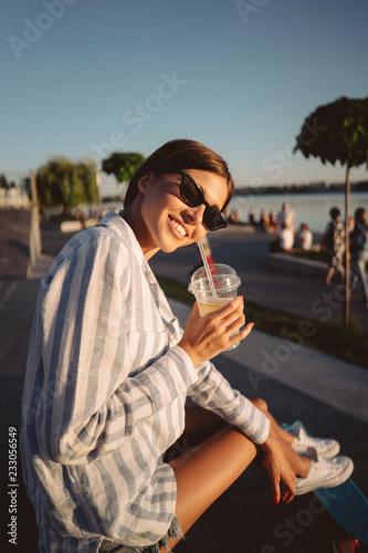 Młoda dziewczyna w okularach przeciwsłonecznych z szkłem lemoniada.