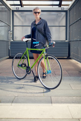 Full-length image of young blonde with green bike near grey wall