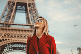 Style redhead girl in red coat and bag at parisian street with view at Eiffel tower in autumn season time © Masson