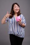 Mature beautiful Asian businesswoman holding piggy bank - 233097165