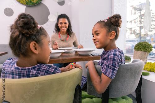 Kręcone siostry. Kręcone siostry noszące te same purpurowe kwadraty sukienki rozmawiają siedząc w restauracji