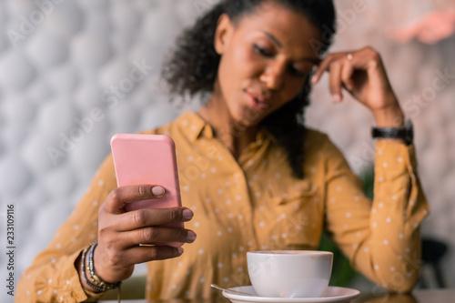 Różowy telefon. Ciemnowłosy piękny elegancki bizneswomanu mienia menchii telefon czyta biznesowego list