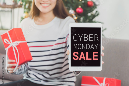 Young beautiful Asian Woman hands holding gift box and smartphone with cyber Monday screen.Smile face in white room background.