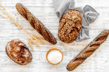 Bakery concept. Fresh brown bread. Loaf and baguette on tablecloth near wheat ears and flour on white wooden background top view