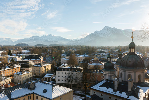 Poster panoramic winter view of the historic center of Salzburg Austria surrounded by the Alps covered with snow in a foggy haze