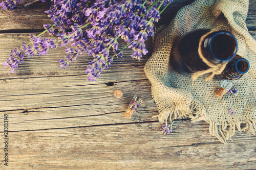 Lavender oil in different bottles on wooden background. Toned image. Top view. - 233133149