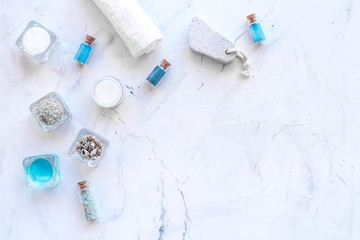 Dead sea cosmetics layout. Sea salt in bottles and bowls near small shells on white stone background top view copy space © 9dreamstudio