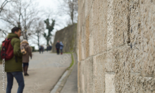 Ancient stone defensive wall of the castle with unrecognized people at background in Budapest