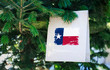 Texas state flag printed on a Christmas shopping bag. Close up of a shopping bag as a decoration on a Xmas tree on a street. New Year or Christmas shopping, local market sale and deals concept.