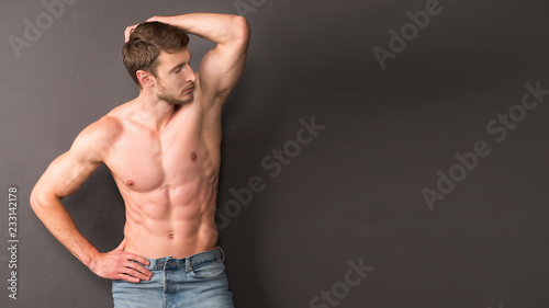 a950ae88c57 One handsome sexual strong young man with muscular body in blue jeans  posing in studio on