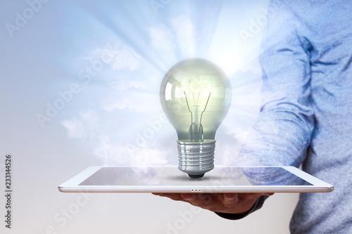 Leinwanddruck Bild Man Hand Tablet PC Idea Bulb
