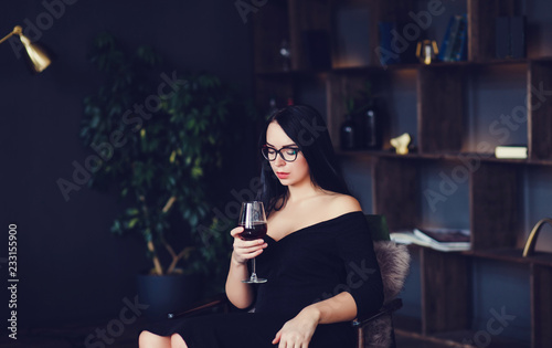 Foto Murales pretty woman in black dress holding a glass of wine while sitting in an apartment