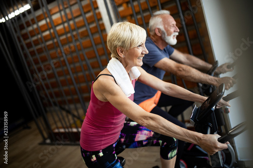 Leinwandbild Motiv Mature fit couple exercising in gym to stay healthy