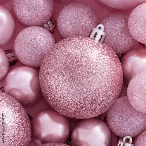 Jasnoróżowa kompozycja na temat nowego roku. Małe dekoracyjne Bożenarodzeniowe piłki dla dekoraci na różowym tle.