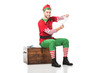 cheerful man in christmas elf costume sitting on wooden chest and holding wishlist isolated on white