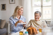 Senior woman in wheelchair with a health visitor sitting at the table at home, eating.