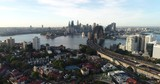 Streets and houses of Kirribilli suburb in view of distant Sydney city CBD landmarks across Harbour waters.  - 233169149