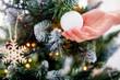 Decorating Christmas tree closeup on hand and Xmas ball