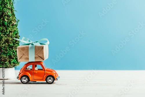 close-up shot of toy vehicle with gift box on blue background - 233177582