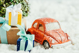 close-up shot of toy car with presents and christmas tree standing on snow made of cotton - 233177978