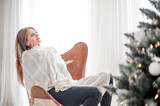 Young relaxed woman sitting on armchair and resting near Christmas tree - 233179170