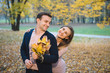 Woman Hugging Man with Yellow Leaves