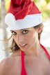 Young woman with Santa Claus hat on Christmas vacation at tropical beach.