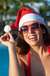 Happy woman on Christmas vacation at tropical resort. Cheerful girl wearing Santa Claus hat and red sunglasses in hotel pool.