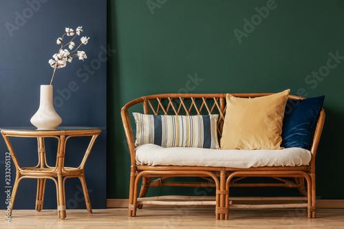 Kwiaty na naturalnym stole obok kanapa z poduszkami w zielonym i niebieskim salonie wnętrza. Prawdziwe zdjęcie