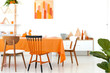 Three different chairs placed by the long dining table with orange tablecloth and dinnerware in real photo of white room interior with rack with decor, simple poster and cupboard with books