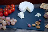 Camembert cheese on a black stone plate with tomatoes, crackers, nuts and grape - 233207165