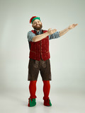The happy smiling friendly man dressed like a funny gnome or elf pointing to left on an isolated gray studio background. The winter, holiday, christmas concept - 233209954