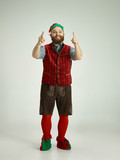 The happy smiling friendly man dressed like a funny gnome or elf pointing up on an isolated gray studio background. The winter, holiday, christmas concept - 233210129
