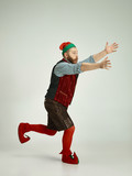 The happy smiling friendly man dressed like a funny gnome or elf running on an isolated gray studio background. The winter, holiday, christmas concept - 233210375