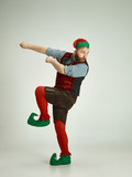 The happy smiling friendly man dressed like a funny gnome or elf pointing to left on an isolated gray studio background. The winter, holiday, christmas concept - 233210530