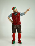 The happy smiling friendly man dressed like a funny gnome or elf posing on an isolated gray studio background. The winter, holiday, christmas concept - 233210738