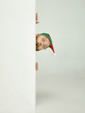 The happy smiling friendly man dressed like a funny gnome or elf posing on an isolated gray studio background. The winter, holiday, christmas concept - 233211334
