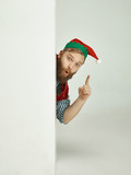 The happy smiling friendly man dressed like a funny gnome or elf pointing up on an isolated gray studio background. The winter, holiday, christmas concept - 233211506