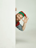 The happy smiling friendly man dressed like a funny gnome or elf posing on an isolated gray studio background. The winter, holiday, christmas concept - 233211554