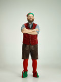 The happy smiling friendly man dressed like a funny gnome or elf posing on an isolated gray studio background. The winter, holiday, christmas concept - 233211935