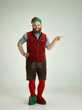 The happy smiling friendly man dressed like a funny gnome or elf pointing to left on an isolated gray studio background. The winter, holiday, christmas concept - 233212133