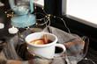 Leinwandbild Motiv Composition with cup of hot winter drink, scarf and Christmas lights near window. Cozy season