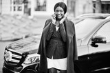 Success stylish african american woman in coat against black business suv car speaking at phone. - 233227913